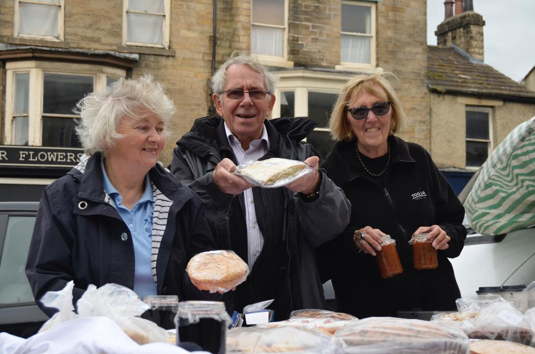 ROARING TRADE: June Addison, Andrew and Christine Bracewell with some of the mouthwatering morsels they had on offer