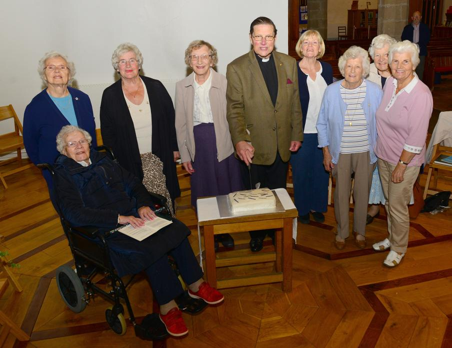 CUTTING THE CAKE: Revd John Moore and his wife Doreen celebrate their diamond wedding anniversary with St Mary's Parish Church's Mothers' Union members		            TM pic