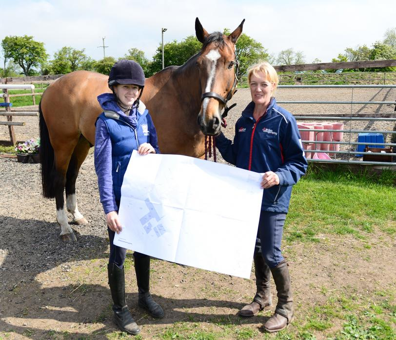 RIDING BOOST: Sarah Tubbs and apprentice Chloe Weller with the plans for the new indoor arena as work got underway earlier this year
