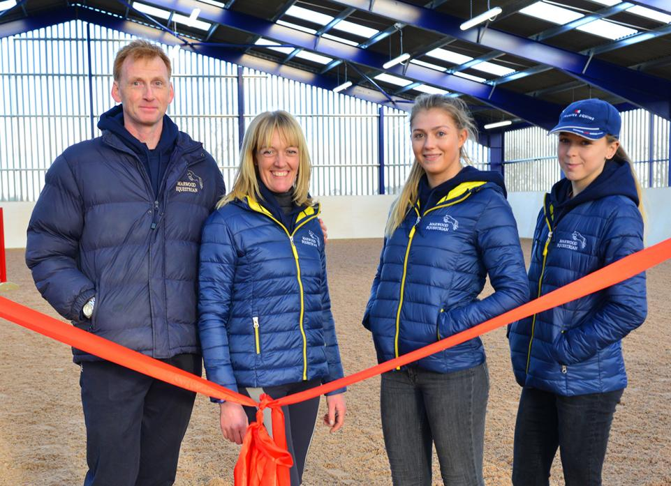 NEW FACILITIES: Anthony and Sarah Tubbs prepare to release the ribbon to open the new indoor show-jumping arena while staff members Juliet Stanger and Chloe Weller look on
