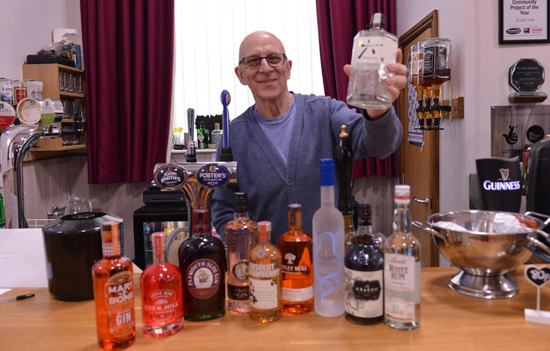 RAISING A GLASS: Volunteer Les Blair with some of the gin, vodka and rum varieties that form part of the Scarth Hall's spirit festival  					              TM pic