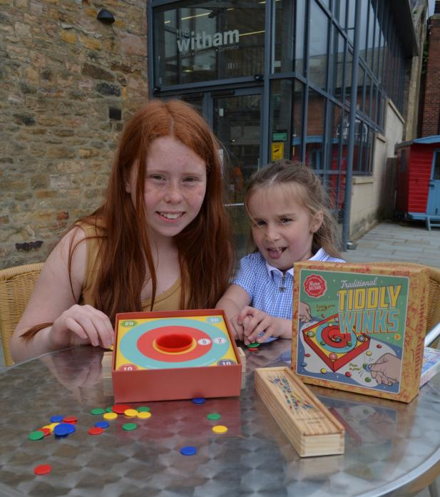 OLD FASHIONED FUN: Young Ella Wallace and Evie Russ-Griffiths try their hand at tiddlywinks for the first time