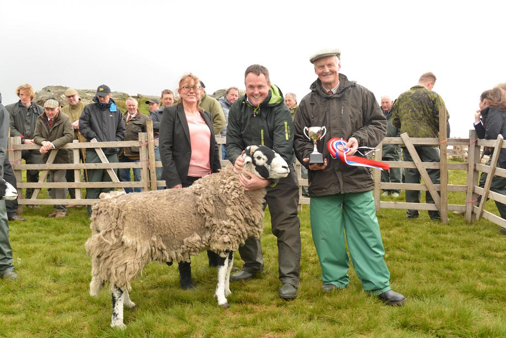 SUPREME CHAMPION: Tan Hill Inn manager Nicola Townsend congratulates Thomas and Stanely Brogden on exhibiting the top Swaledale sheep in the annual show