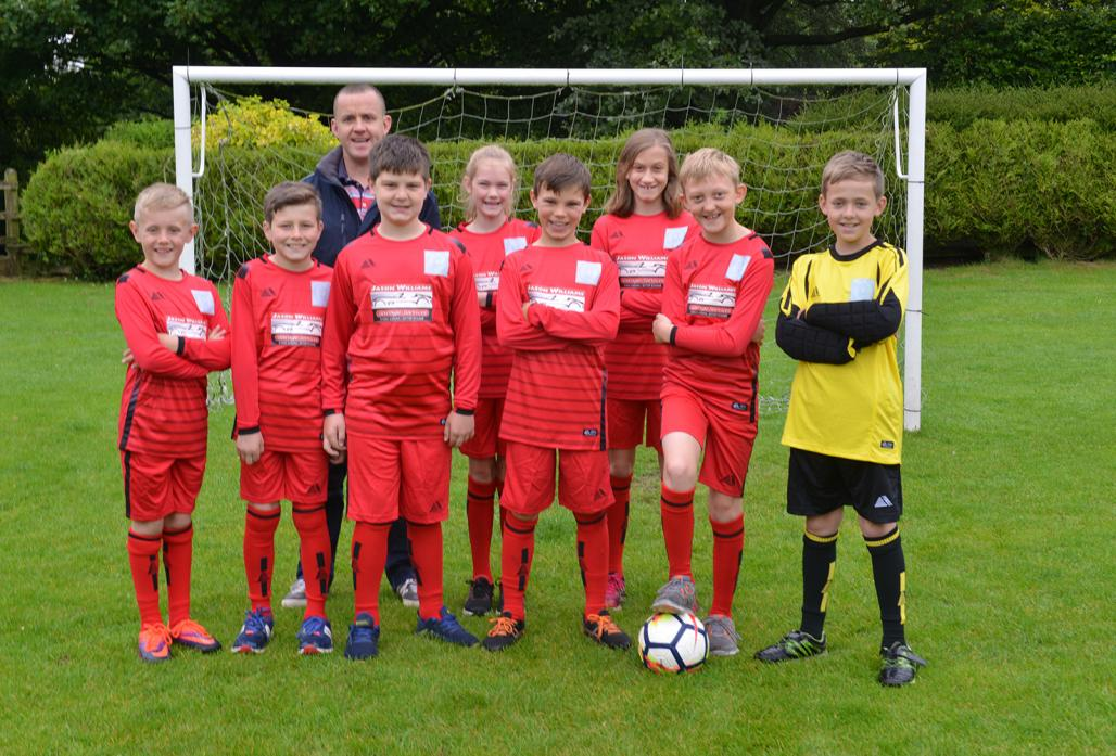 NEW STRIP: Businessman and coach Jason Williams with the newly kitted out Bowes Hutchinson's football team of Luke, Jack, Theo, Lily, Aidan, Heidi, Elliott and Kian