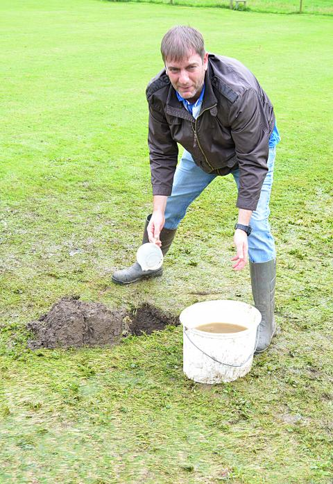 HOLE LOT OF TROUBLE: Cliffe skipper Richard Jameson attempts to clear the water after a burst pipe flooded part of the Piercebridge club's outfield