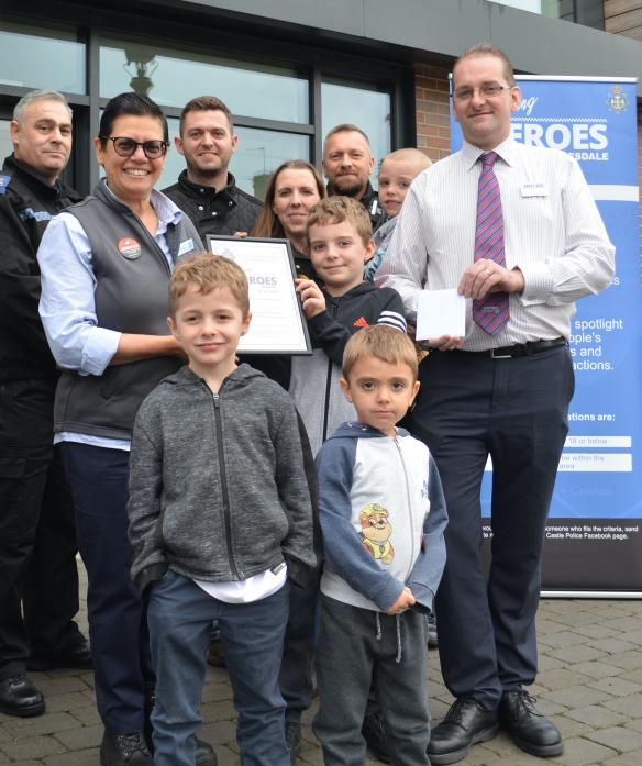 OUR HERO: Benjamin Hawksby received his Local Hero award from scheme supporters Naila Laundy (Co-op) and Alex Wood (Boyes). At the front are Oliver, 7, and four-year-old Joseph while behind are PC Paul Conroy, dad Daniel and mum Susanne holding Joshua and