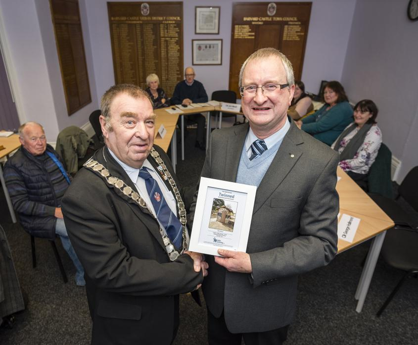 FLUSHED WITH SUCCESS: Ian Blake hands a certificate to mayor Cllr John Blissett ahead of last week's town council meeting