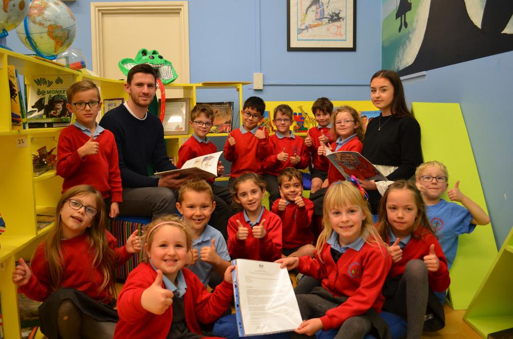 TOP MARKS: Pupils were delighted to receive a letter congratulating them on their English learning skills. They are pictured with teacher Alex Dougall and teaching assistant Claudia Hollywell