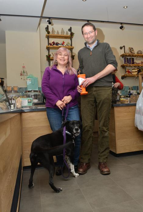 TOWN SCHEME: Adele Tyler and her dog Hugo deliver the first Alzheimer's Research UK collection tin to Chocolate Fayre's Kenny Walker