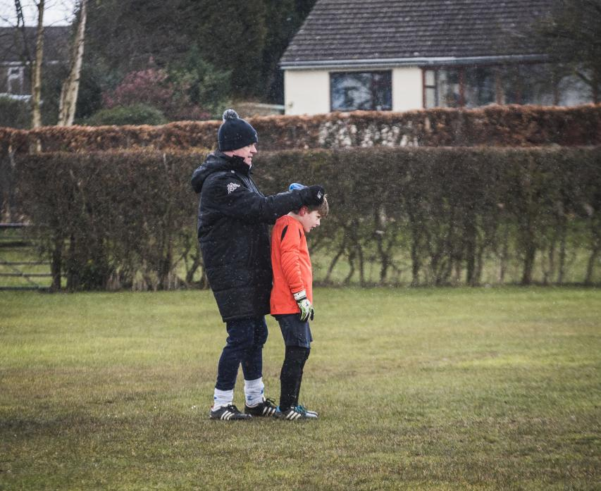 Manager Mel Thwaites makes sure the goalie is warm on a wet and cold day