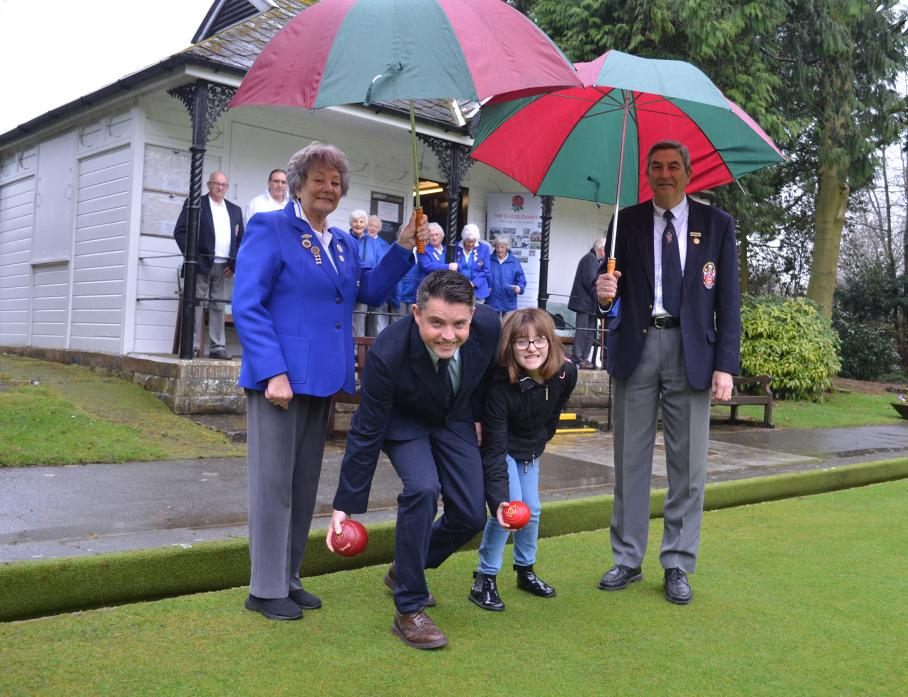 GIMME SHELTER: Barnard Castle Bowls Club president John Tallentire and lady president Gillian Harle provide some shelter as Matthew Croom and daughter Lily send down the ceremonial first bowls of the season