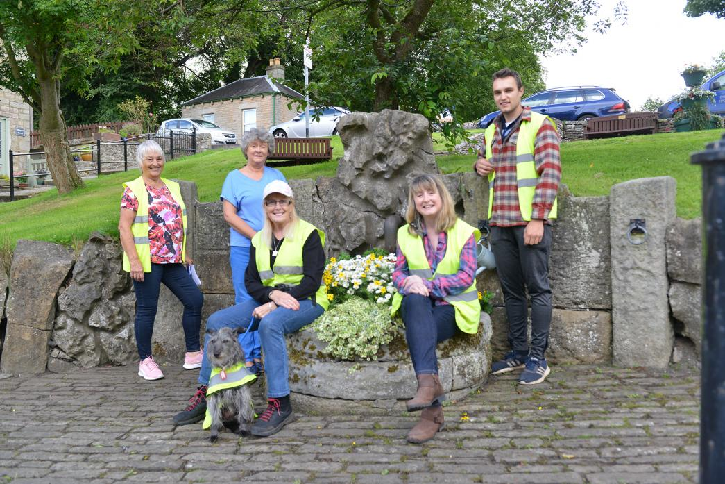 AT WORK: Middleton-in-Bloom volunteers Pam Phillips, Lindsey Peppel, Jo Lee, Christine Cartwright, Harry Bowron and mascot Maisey with one of the planters they have filled with brightly coloured flowers on Seed Hill