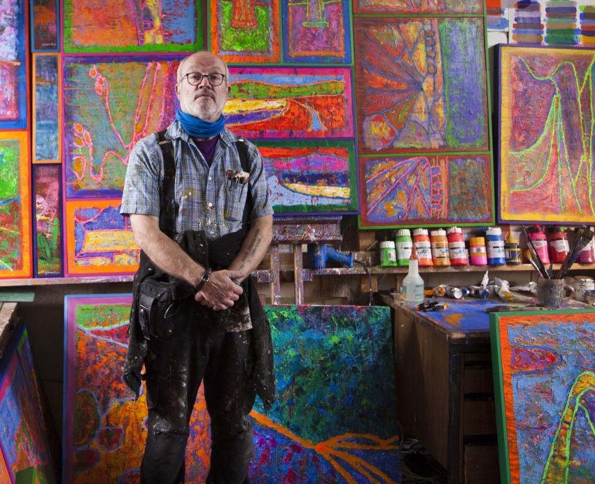 COLOURFUL SCENE: Simon Pell with some of his paintings he has produced during lockdown