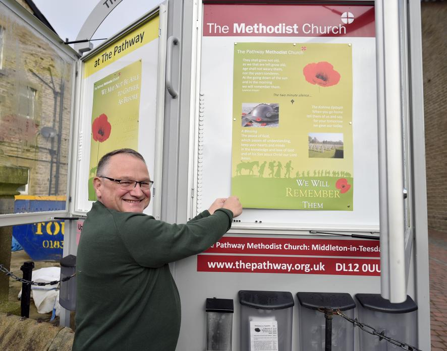 ARTISTIC TALENT: Revd Graham Cutler puts up one of the posters he made for Remembrance Sunday after plans to mark the day with a service had to be abandoned