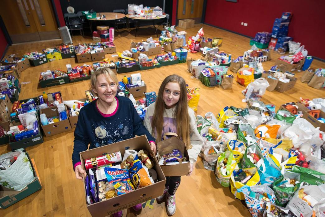 SUPPORTING THE COMMUNITY: Rachel Tweddle, chief executive of the TCR Hub, with daughter Amelia Robinson and some of the thousands of care packages that have been distributed during the past year