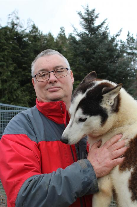 STRONG BOND: Steve Grinham with one of his team of Siberian racing huskies, which he keeps at home in Hamsterley Forest