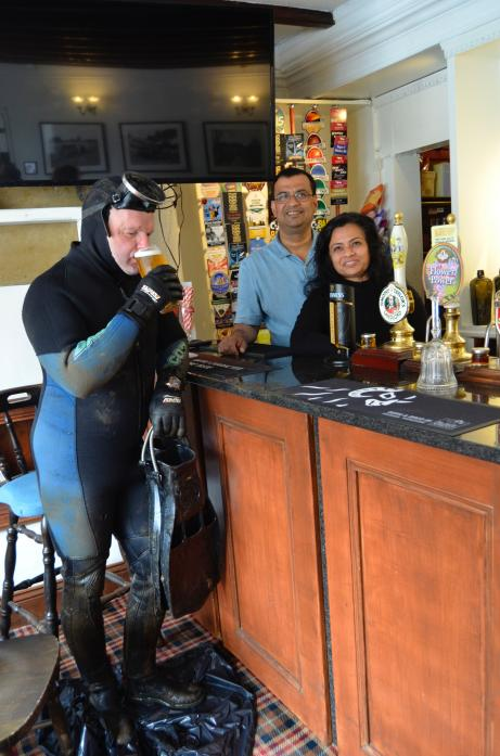 THIRSTY JOB: Landlord and landlady Roy and Rima Chatterjee recreate the 1969 frogman photograph with Ian Mitchell